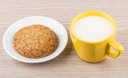 Één koekje in schotel en gele kop van melk Royalty-vrije Stock Afbeeldingen
