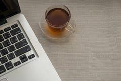 Één kop thee is op de rechterkant van laptop stock afbeelding