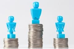 Één mannetje en twee vrouwelijke beeldjes die zich op stapels van muntstukken bevinden Stock Foto