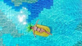 Één meisje die op een rubbermatras in een pool liggen Van de overzeese het concept Luxevakantie stock videobeelden