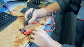Één mens controleert een voltage van computerapparatuur, omhoog sluit