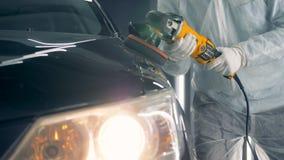 Één mens in eenvormig houdt een speciale schijf terwijl het oppoetsen van een auto 4K stock video