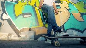 Één mens rolt een skateboard met een been terwijl het rusten Langzame Motie stock videobeelden
