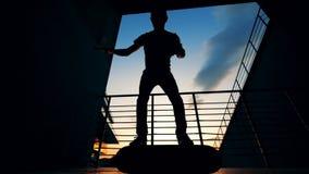 Één mens springt op een skateboard en bevindt zich op het terwijl het doen van trucs Langzame Motie stock video