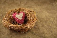 Één met de hand gemaakt hart in het nest Stock Afbeeldingen
