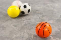 Één nieuwe rubber zachte basketbalbal op achtergrond van drie verschillende sportenballen stock afbeelding