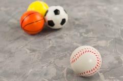 Één nieuwe rubber zachte honkbalbal op achtergrond van drie verschillende sportenballen stock fotografie