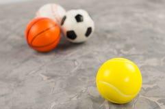 Één nieuwe rubber zachte tennisbal op achtergrond van drie verschillende sportenballen royalty-vrije stock fotografie