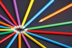 Één oranje potlood die van de cirkel van andere kleurrijke potloden op de donkere achtergrond duidelijk uitkomen royalty-vrije stock foto