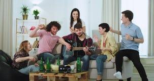 Één paar heeft thuis een partij met hun vrienden in woonkamer op gitaar het grappige dacing zingen en zij die zo voelen stock video