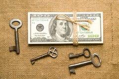 Één pak dollars klopte met kabel, muntstukken en sleutels in de oude doek Stock Foto's