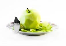 Één pelde groene appel met mes op een witte plaat en een witte achtergrond - vooraanzicht Stock Foto