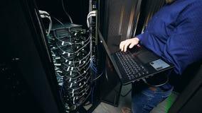 Één persoon controleert datacentrummateriaal, die met laptop werken stock videobeelden