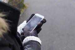 Één persoon die een smartphone met handschoenen proberen te openen Stock Fotografie