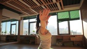 Één persoonlijke trainer die asanas doen die op matwerk in yoga'sstudio blijven stock video