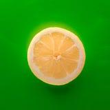 Één plak van citroen op rode achtergrond, regelt schot royalty-vrije stock foto's