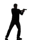 De moordenaarspolitieagent die van de mens kanon bevindend silhouet streven Royalty-vrije Stock Foto's