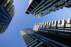 Één puntperspectief die recht omhoog naar duidelijke blauwe hemel van grondniveau van lange wolkenkrabbergebouwen in Milaan, Ital Stock Foto's