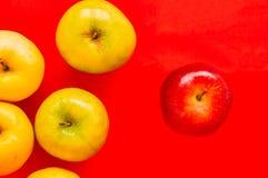 Één rode appel die van een groep andere appel op een rood duidelijk uitkomen Stock Foto's