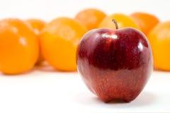 één rode appel en bos van sinaasappelen Stock Afbeeldingen