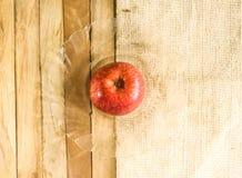 Één rode appel op glasplaat met hout en matachtergrond Stock Foto's