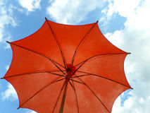 Één rode gekleurde parasol tegen levendige blauwe hemel en witte wolk Royalty-vrije Stock Fotografie