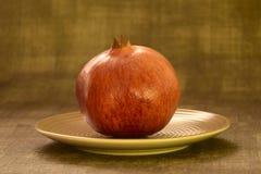 Één rode granaatappel op een ceramische plaat stock afbeeldingen