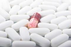 Één rode pil in vele witte pillen Stock Afbeeldingen