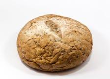 Één rond die korrelbrood op een witte achtergrond wordt geïsoleerd Geheel vers tarwe en rogge klein brood met heel wat zaden Stock Foto