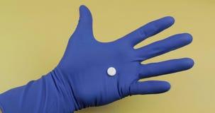 Één ronde witte pil ter beschikking gekleed in rubber steriele medische handschoen stock footage