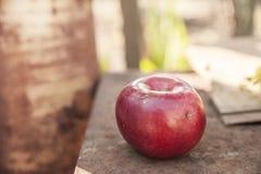 Één rood appel dichte omhooggaande en exemplaarruimte op de achtergrond van een roestige lijst Een lelijke appel met verrotting royalty-vrije stock foto