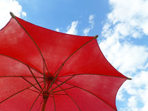 Één rood gekleurd zonnescherm tegen levendige blauwe hemel en pluizige witte wolken Stock Fotografie