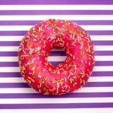 Één roze fruitdoughnut op gestreepte purpere en witte strepen achtergrond hoogste menings dichte omhooggaand stock foto