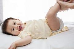 Één samile kleine die de veranderingsluier van het babymeisje op wit wordt geïsoleerd Stock Foto's