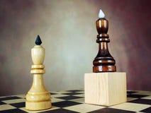 Één schaakkoning heeft een voordeel over een andere omdat hij zich op een houten tribune bevindt stock foto's