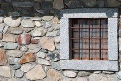 Één steenvenster van een chalet met metaal vierkante roosters royalty-vrije stock afbeelding