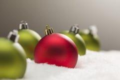 Één Uniek Rood met Groene Kerstmisornamenten op Sneeuw Stock Foto's