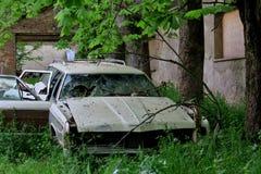 In één van de bossen in Europa de oude geslagen en vergeten auto's in de yard stock fotografie