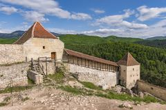 Één van de ingangen in de oude middeleeuwse vesting van Rasnov, in Brasov-provincie Roemenië, met bossen en bergen op de achtergr stock foto's
