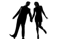 Één van de paarman en vrouw het lopen holdingshanden stock foto
