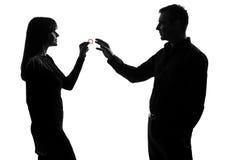 Één van de paarman en vrouw holding die condoom geeft Stock Foto