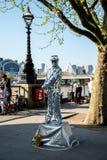 Één van de straat kleedde omhoog uitvoerders dichtbij Jubileumtuinen en het wiel van de het Oogobservatie van Londen stock fotografie