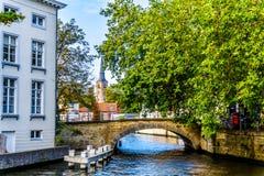 Één van de vele kanalen met de steen overspant bruggen in historisch Brugge, België stock foto's