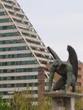 Één van de vier gargouilles custod van de brug van het koninkrijk van Valencia met een piramidaal modern gebouw op de linkerzijde Stock Fotografie