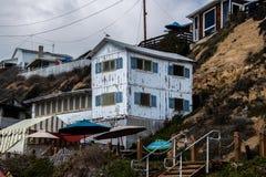Één van verscheidene huizen in verval die langs het strand en de kustlijn van Crystal Cove zoals die op deze datum worden gezien  stock fotografie