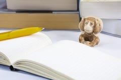 Één vermoeide stuk speelgoed aap met blocnote en potlood en vele dikke boeken Royalty-vrije Stock Fotografie
