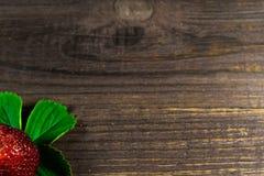 Één verse rijpe aardbei met groen blad op oude houten backgrou Stock Foto