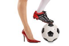 Één voet in high-heeled schoen en andere in voetbalschoen Stock Foto