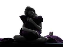 Het koesteren van de vrouw slaperige hoofdkussenzitting op bedsilhouet royalty-vrije stock fotografie