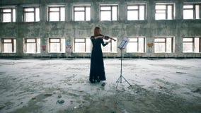 Één vrouw speelt een viool, die zich in een geruïneerd gebouw bevinden stock video